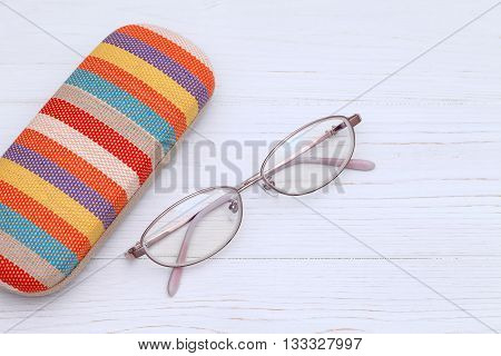 Ladies glasses and case on the white wooden table