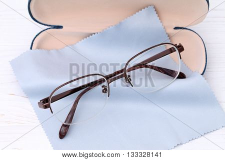 Glasses and case with glasses cleaning cloth on white wooden table