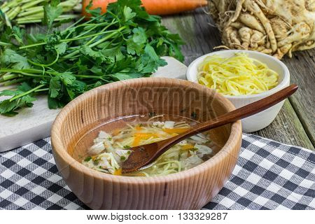 Chicken Broth with Carrots Celery Parsley and Noodle in Wooden Bowl with Spoon on a Old Wooden Table