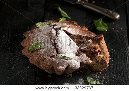 Chocolate cake with cherry on a black surface (sprinkled with powdered sugar). Horizontal orientation
