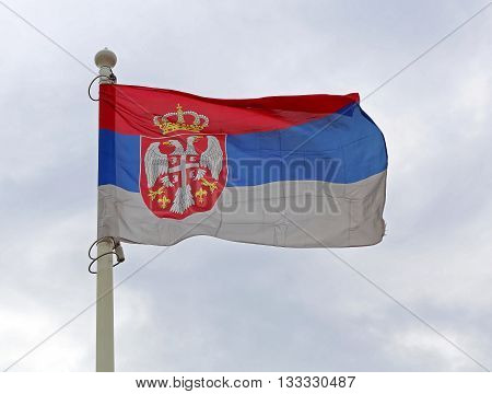 Serbian Flag at Flagpole Flying at Wind