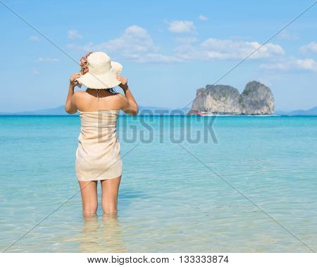 Asian Woman Wearing Summer Hat And Sarong On A Tropical Beach Looking Toward Boat And Island.