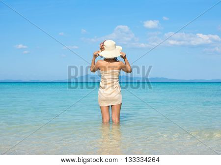Woman Wearing Sarong And Hat On Tropical Beach.