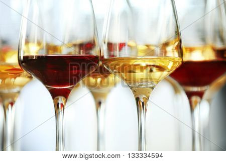 Many glasses of different wine on a table, close up
