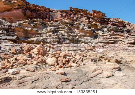 Rugged terrain at Pot Alley gorge with natural red sandstone formations under blue skies in Kalbarri, Western Australia.