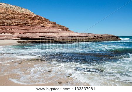 Turquoise Indian Ocean waters, sandstone rock cliffs and secluded inlet at Pot Alley under clear blue skies in Kalbarri, Western Australia.