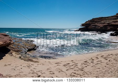 Turquoise Indian Ocean seascape with waves rushing the the secluded cove with sandy beach at Pot Alley under clear blue skies in Kalbarri, Western Australia.