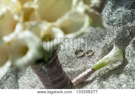 Wedding bouquet of white Calla Marsh Marsh, Bog Arum, Water-Arum, Araceae family. the light of the morning sun, the newlyweds rings