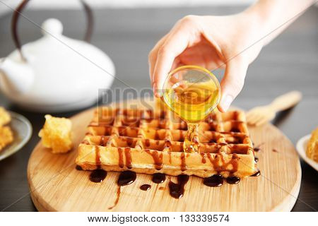 Female hand pouring honey on waffles