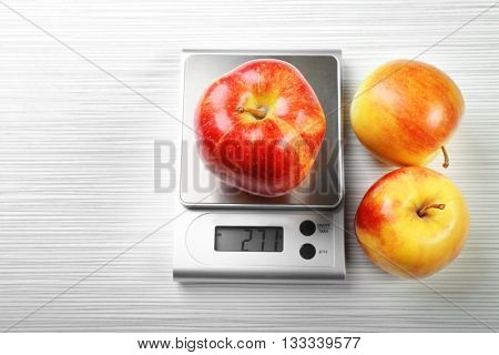 Apple with digital kitchen scales on wooden background