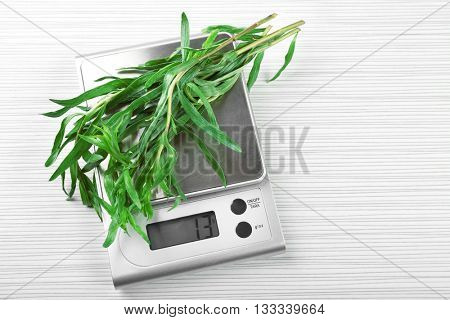 Herbs with digital kitchen scales on wooden background