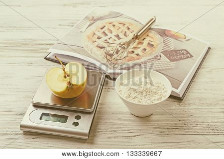 Making apple pie. Using digital kitchen scales on wooden table. Cooking apple cake concept