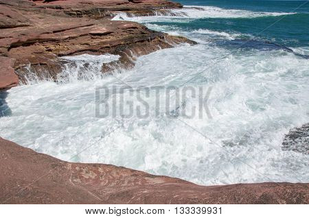 Coastal recess with foamy Indian Ocean waters rushing the sandstone formations at Pot Alley gorge in Kalbarri, Western Australia.
