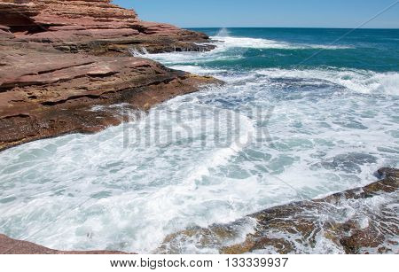 Coastal recess with Indian Ocean seascape and sandstone cliffs at the stunning Pot Alley gorge in Kalbarri, Western Australia.