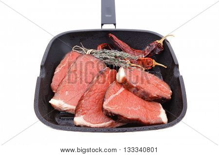 raw beef meat fillet on bbq pan with cayenne pepper isolated on white background