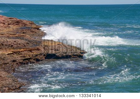Turquoise Indian Ocean waves rushing the coastal outcroppings at Pot Alley under clear blue skies in Kalbarri, Western Australia.