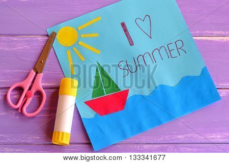 Paper card with ship, sun, sea. I love summer. Kids summer camp idea for crafts and activity. Inspiration for children of all ages. Paper art children project. Scissors, glue stick. Wooden background