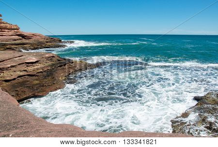 Turquoise Indian Ocean waves rushing the coastal sandstone formations that create the recess at Pot Alley under clear blue skies in Kalbarri, Western Australia.