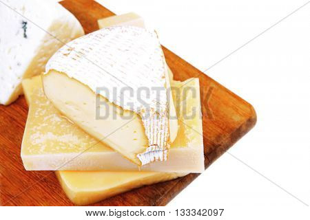 solid french cheese parmesan brie and edam on wooden platter isolated on white background