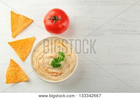 Ceramic bowl of tasty hummus with chips and parsley on table