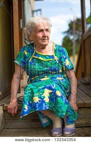 Old woman sitting on the porch of rural house.