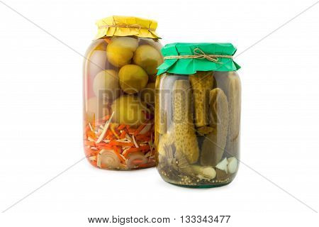Homemade pickled green tomatoes with cucumbers, carrots and onions in glass jar with paper wrapper. Homemade preserves, pickles. Jar of canned green marinated tomatoes and cucumbers isolated on white