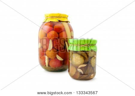 Homemade pickled red tomatoes with cucumbers, garlic and pepperin glass jar with paper wrapper. Homemade preserves, pickles. Jar of canned marinated tomatoes and cucumbers isolated