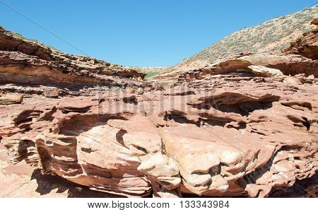 Rugged landscape at Pot Alley gorge with red sandstone dotted with native flora under clear blue skies in Kalbarri, Western Australia.