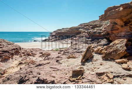 Remote inlet at the Pot Alley gorge with natural sandstone rock formations and Indian Ocean waters under a clear blue sky in Kalbarri, Western Australia.