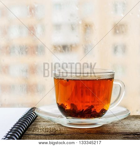 Black tea in cup of glass on the windowsill with a notebook and pencil on a rainy day close-up
