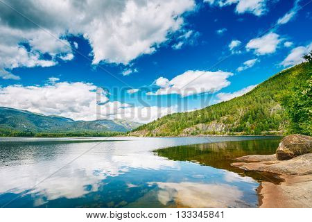 Beautiful Norwegian Mountains and Blue Deep Lake. Nature of Norway. Travel and Hiking. Amazing Scenic View. Nobody. Scandinavia. Reflections Of Sky In Water Surface.
