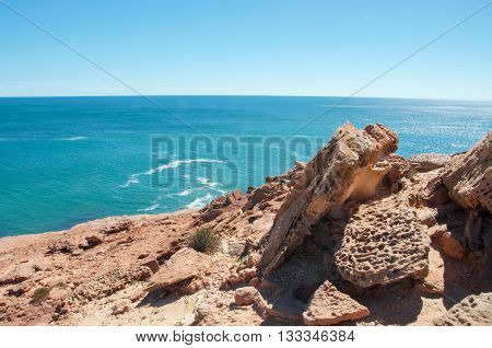 Elevated view from sandstone bluffs over the turquoise Indian Ocean seascape on a clear day at Pot Alley in Kalbarri, Western Australia.