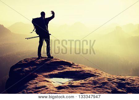 Hiker On Peak. Backpacker With Poles In Hand Shadowing Eyes, Spring Daybreak