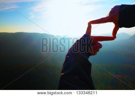 Close Up  Hands Make Frame Gesture. Blue Misty Valley Bellow Rocky Peak. Sunny Spring Daybreak