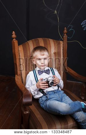 A Little Boy Sit In Armchair And Holds Photo Camera In His Hands
