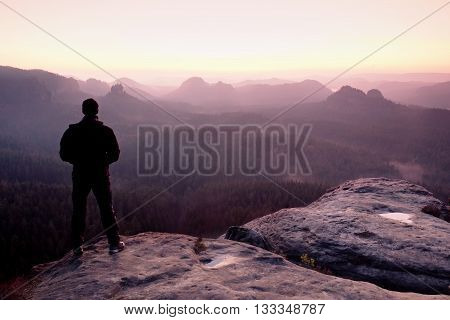 Tall Man In Black On Cliff And Watch To Mountain Sunrise.silhouette In Selfconfident Pose
