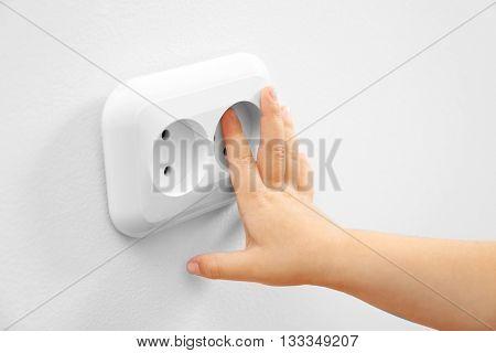 Little child putting finger in power socket, closeup