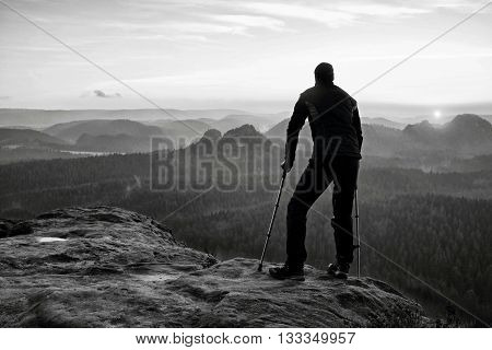 Tourist With  Medicine Crutch On Mountain Peak. Deep Misty Valley Bellow Silhouette Of Ma