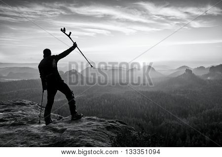Hiker With  Medicine Crutch Above Head Achieved Mountain Peak.