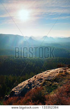 Rocky Gulch Full Of Gentle Fog And Sun Is Hidden In Heavy Mist. Sharp Cliffs