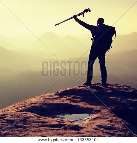 Hiker With Crutch Above Head. Deep Valley Bellow Man Silhouette