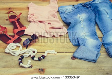 Women's summer clothing and accessories: tank top, jeans, sunglasses, belt, shoes on wooden background.Toned image.