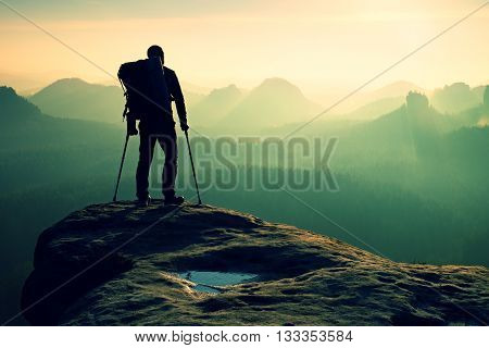 Tourist With Leg In Immobilizer. Hiker Silhouette With Medicine Crutch On Mountain