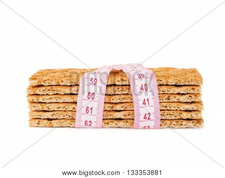 Diet Crispbread and measuring tape isolated on white. Diet concept