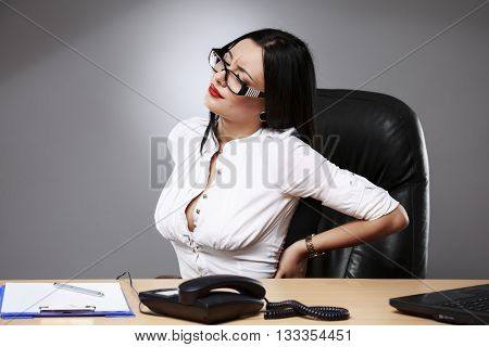 Business women having back pain at office workplace