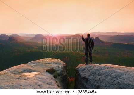 Hiker Stand With Smart Phone On Top Of Mountain And Enjoying Spring Sunrise. Tourist Guide