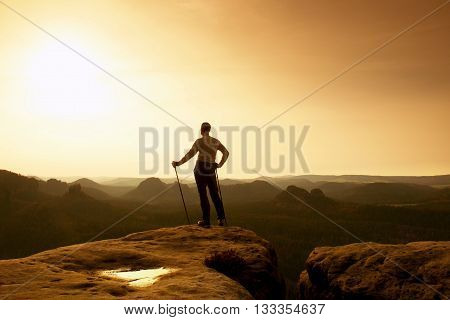 Ginger Hair Man In Grey T-shirt And Dark Trekking Trousers On Sharp Rock. Tourist With Pole Above Mi