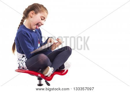 Happy little girl sitting on a chair and using a tablet computer, isolated on white background