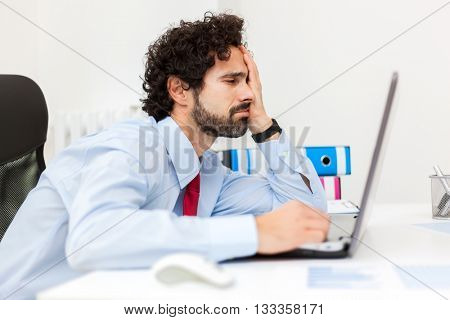 Bored businessman working at his laptop
