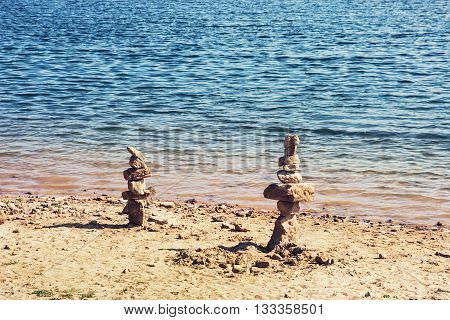 Towers of stone on the lakeside. Natural scene. Pile of stones. Travel destination. Zen stones. Pyramid stack. Interesting place.